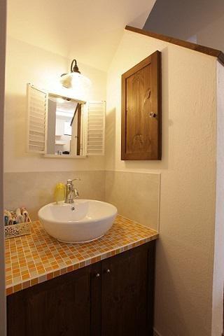 タイル貼りの天板に手洗器をのせた洗面化粧台:画像