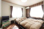 木目調の壁が床材やクロスとマッチし、落ち着きのある寝室:画像
